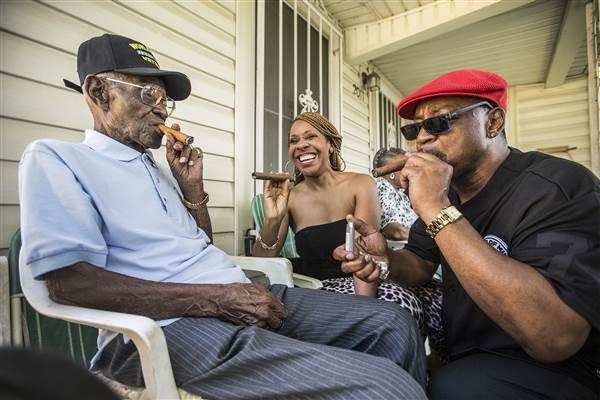 Richard Overton, left, smokes a cigar with a few neighborhood friends Donna Shorts, center and Martin Wilford Sunday, May 3, 2015, in Austin, Texas. Ricardo B. Brazziell / Austin American-Statesman via AP file