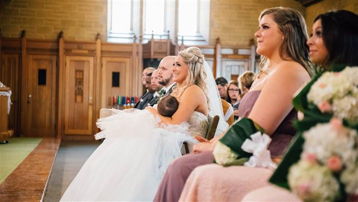 With a big smile on her face, Christina Torino-Benton nurses her 9-month-old daughter during her wedding ceremony in Montreal. Lana Nimmons Photograpy