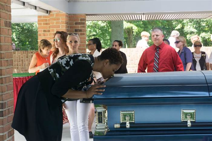 Jaspen Boothe kissing Serina Vine's casket. Courtesy of Catherine Rae Photography