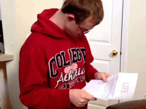 Rion Holcombe opens his acceptance letter. CBS NEWS