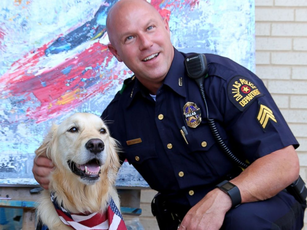 A comfort dog poses with a police officer at the Dallas Police Headquarters.