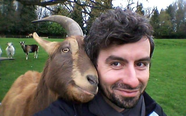 Dr Christian Nawroth with a goat during his research, which suggested that goats could communicate with humans in the same way as cats or dogs. CREDIT: CHRISTIAN NAWROTH