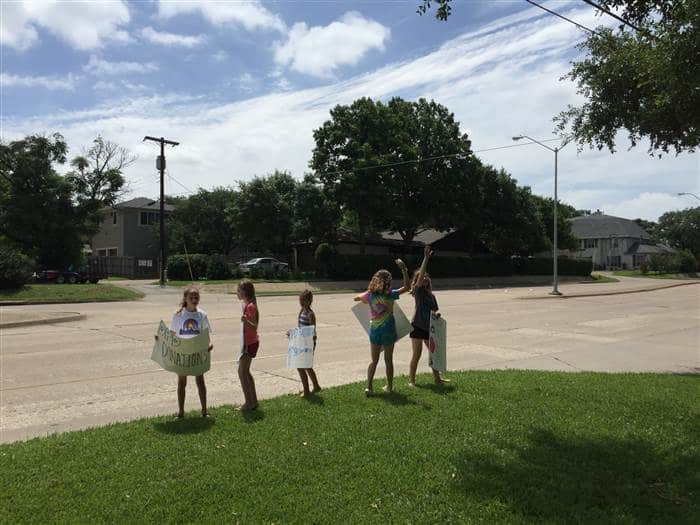 The girls flagging down cars to come to their lemonade stand. Courtesy of Kimberly Nelon