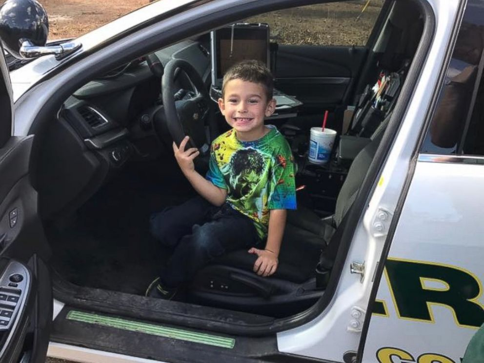 A Walton County, Florida, boy sits in a police cruiser after calling 911 to invite police officers to Thanksgiving Dinner. Walton County Sheriffs Office