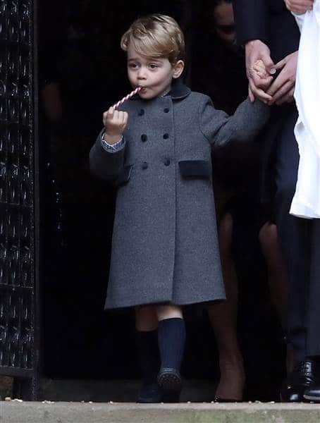 Prince George got in the Christmas spirit by sucking on a candy cane following a service at St Mark's Church in Englefield, Britain. Reuters