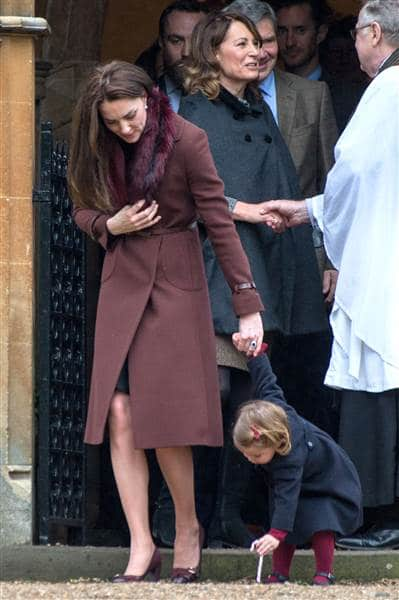 Princess Charlotte, 2, elected to use her candy cane as a digging tool instead of a sweet as she came out of church with Duchess Kate. REX via Shutterstock