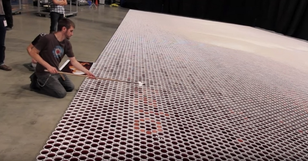 He Lines Up 66,000 Water Cups On Floor. When The Camera Pans Out…Wow