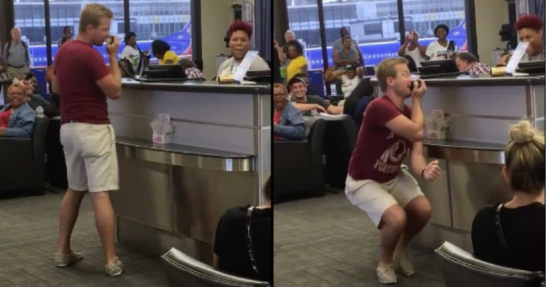 Passenger Grabs Microphone At Airline Counter. When He Starts To Sing She Grabs Her Camera