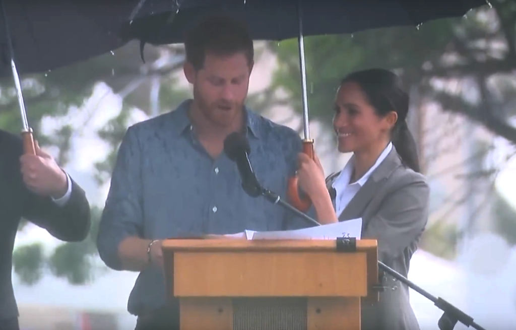 The Duchess of Sussex hold the umbrella for the Duke