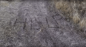 HELP written in the dirt by Katie Ogle