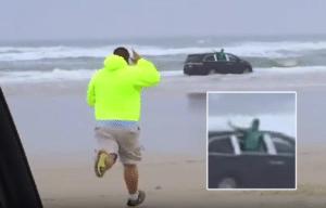 Tim Tesseneer runs for the minivan driven by Ebony Wilkerson as she drives into the Atlantic Ocean