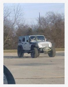 A Silver Jeep Wrangler sits isolated in the parking lot
