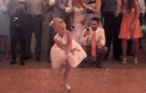 Flower girl having a blast dancing at wedding reception