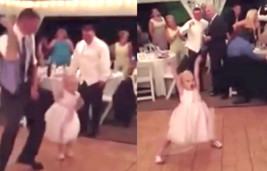 Flower girl having a blast dancing at wedding reception