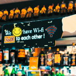 """sign saying """"we have Wi-Fi, talk to each other"""" with a smiley face in a virtual bar"""