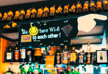 "sign saying ""we have Wi-Fi, talk to each other"" with a smiley face in a virtual bar"